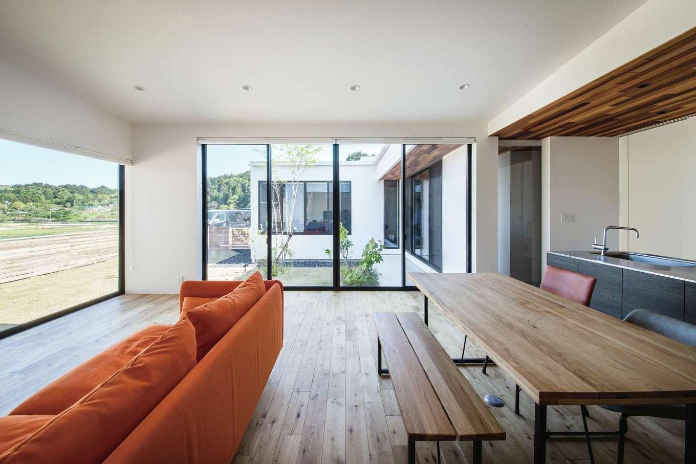 インフィルプラス【デザイン住宅、平屋、ガレージ】大きな窓から中庭や対面の寝室、周囲の風景を見渡せる開放的なLDK。「これ程の大開口でも、地震に強い構造を維持できるところが『SE構法』のスゴさだと思います」とご主人