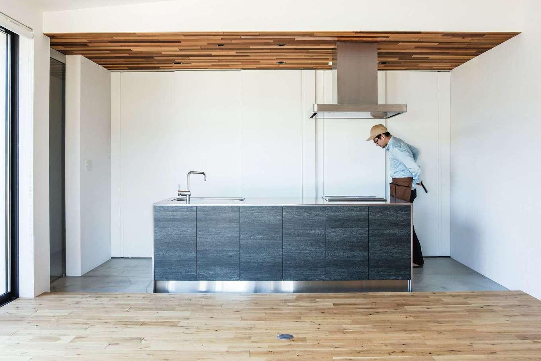 インフィルプラス【デザイン住宅、平屋、ガレージ】キッチンはアイランド型を採用。背面の白い扉の収納に生活感をすべて仕舞い込むことで、美しい空間を維持できる