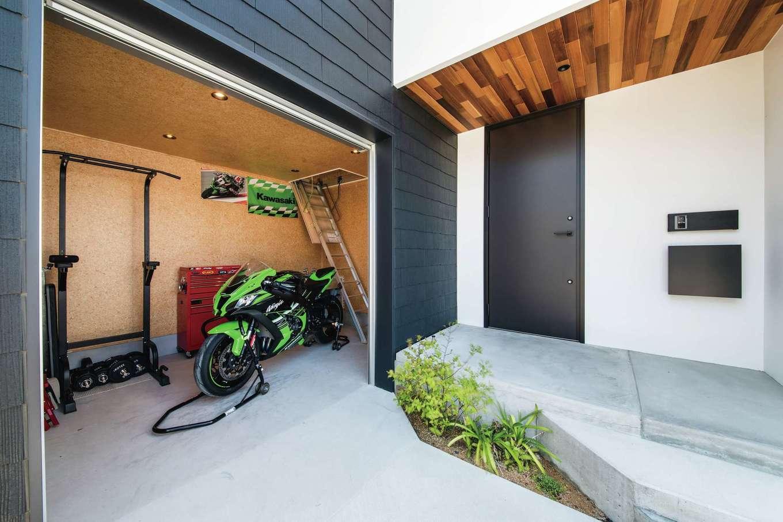 インフィルプラス【デザイン住宅、平屋、ガレージ】玄関脇のバイクガレージは6畳の広さがあり、庫内でバイクの手入れも可能。梯子の上にはロフトがあり、夫妻の趣味のアウトドア用品をまとめて格納