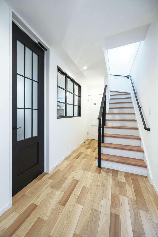 irohaco (アヴァンス)【デザイン住宅、子育て、間取り】LDKと同じく、モノトーンナチュラルにコーディネートされた玄関ホール。ダイニングの格子窓から階段が見えるのもポイント