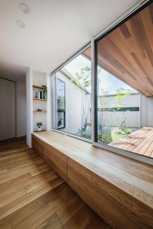 ワンズホーム【浜松市浜北区小松3044-1付近・モデルハウス】廊下の大きな窓が、陽の光をたっぷりと家の中へ招き入れ、いつでも中庭のやわらかな空気を感じさせてくれる。収納としても便利な窓際のベンチに腰掛けて、窓の外を眺めながらひと休み
