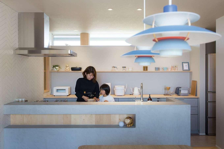 デザインハウス【デザイン住宅、趣味、インテリア】モールテックスの腰壁で覆ったキッチン。背面の棚には小物や器をディスプレイ。ダイニングのPHランプを中心にカラーをコーディネートし、統一感に溢れた空間が美しい