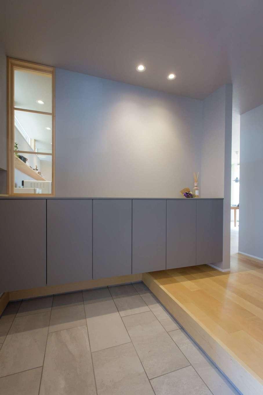 デザインハウス【デザイン住宅、趣味、インテリア】ニュアンスカラーでコーディネートした玄関。内窓からキッチンの様子が見え、奥さまが家族を笑顔で出迎える