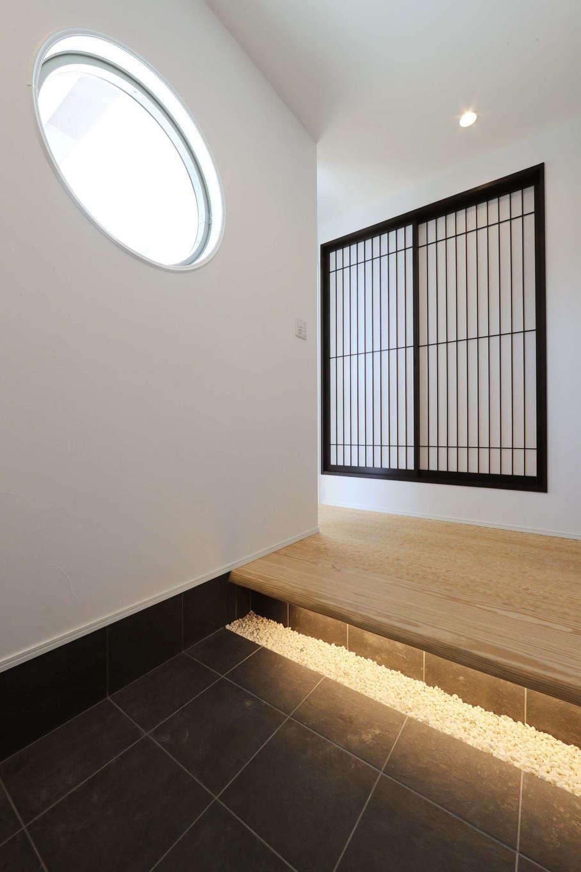 日本住建【デザイン住宅、和風、間取り】和の情緒たっぷりの玄関。丸窓から差し込むやわらかな光が、うづくり仕上げの床を照らし、訪れる人を和ませる