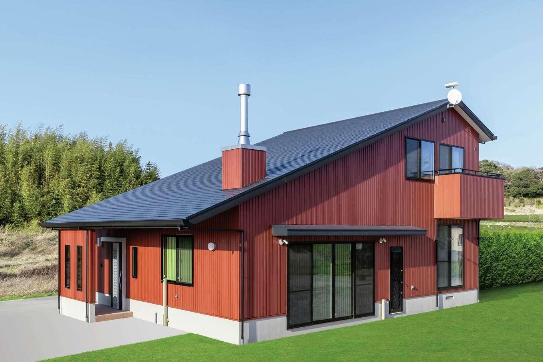 住まいるコーポレーション【自然素材、夫婦で暮らす、間取り】200坪の敷地に建つ2階建て。レンガ色のガルバリウム鋼板の外壁が周囲の緑に映える。さらに、大屋根や煙突がカナディアン風の雰囲気を醸し出している