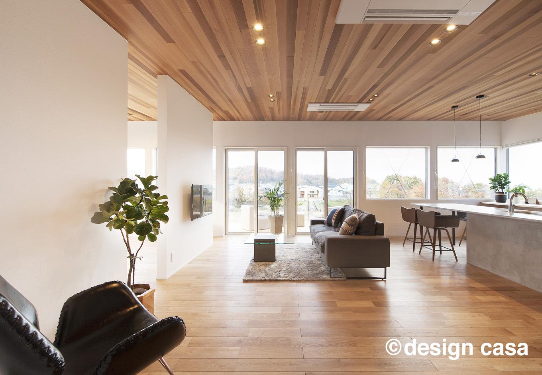 Um House(マル祐戸田建築)【design casa(デザイン カーサ)】レッドシダー張りの天井と白壁でメリハリをつけたリビング。大開口から光と風を心地よく取り込んでいる