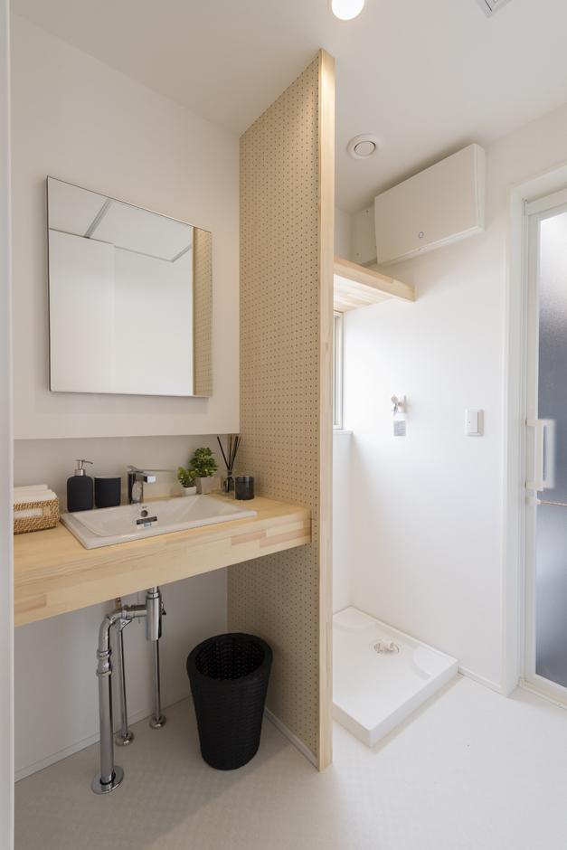 Um House(マル祐戸田建築)【Rational Box(ラショナル ボックス)】木目のカウンターと仕切り壁がナチュラルでさわやかな印象の洗面スペース