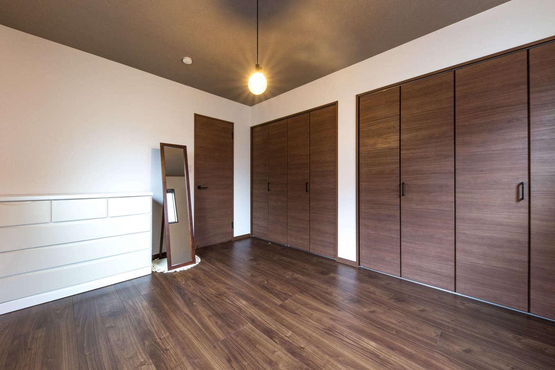 建築システム(狭小住宅専門店)【1000万円台、狭小住宅、インテリア】夫婦の寝室はシンプルに。壁一面はクローゼットにして収納スペースを確保。天井にはアクセントクロスを用いてシックに整えた