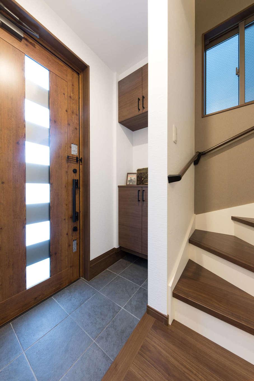 建築システム(狭小住宅専門店)【1000万円台、狭小住宅、インテリア】玄関はホールをなくしてスペースを節約。たたきの石板タイルが室内のヴィンテージインテリアと調和している。玄関ドアは採光ができるタイプにして閉塞感を軽減
