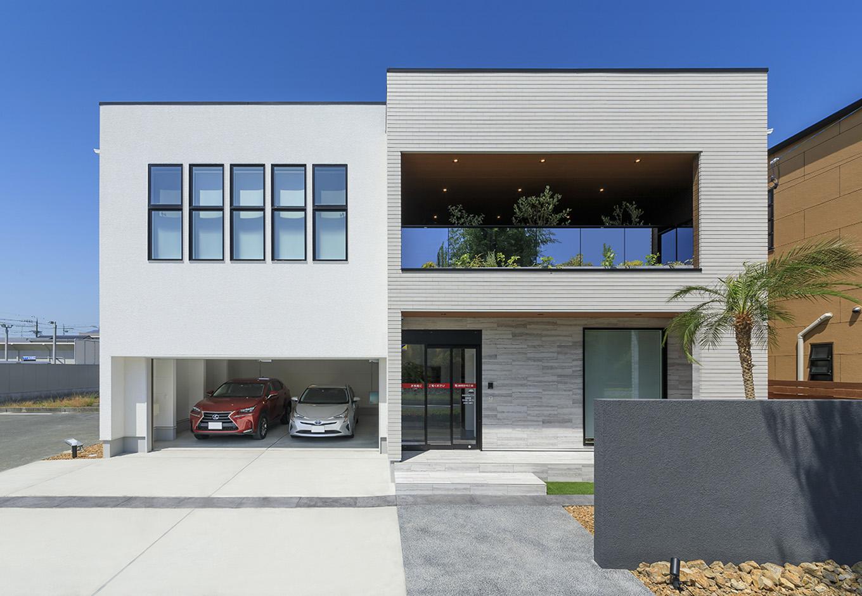 納得住宅工房【浜松市中区新津町615-1・モデルハウス】ヤシの木、テラスバルコニーからのぞく観葉植物に、キューブ状の建物が2つ連なった外観デザインは、モナコのリゾートホテルをイメージ。白を基調としながら、のっぺりと単調に見えない理由は、随所に効かせた黒い縁取りや木目をアクセントに、装飾性のある壁やタイルでニュアンスを出しているため