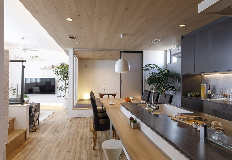 納得住宅工房【浜松市中区新津町615-1・モデルハウス】2階LDKは、キッチンの天板や食器棚を黒にしてアクセントを効かせつつ、全体的に白を基調としたナチュラルなアースカラーで統一。天井の白木と無垢フローリングがダイニングテーブルと調和した空間は、北欧のリゾートホテルさながらの雰囲気
