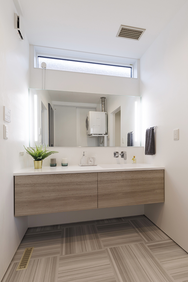 納得住宅工房【浜松市中区新津町615-1・モデルハウス】白を基調に、ナチュラルなアースカラーを合わせてやさしいテイストに仕上げた洗面室。洗練されたデザインの洗面台はイタリアのメーカー「CASA BATH」社製。ハイサイドライトに加え、フローリングと面材をグレーで統一したことで、自然で明るいラグジュアリーな空間になった