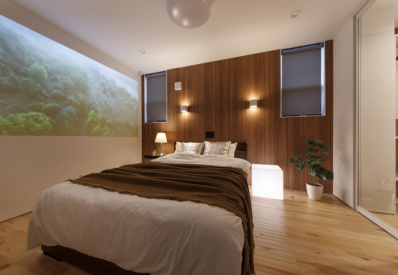 納得住宅工房【浜松市中区新津町615-1・モデルハウス】1階の主寝室。プロジェクターが設置されており、壁をスクリーンのように使うこともできる。コストを抑えるため、床は集成材を使用しているが、表面に厚さ3mmの無垢材を貼っているのでまったく遜色ない