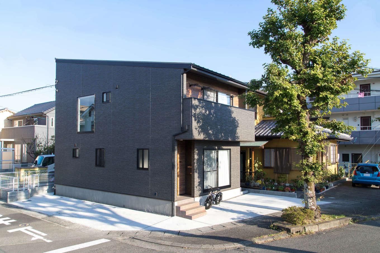 建築システム(狭小住宅専門店)【1000万円台、収納力、間取り】シルバーブラウンのガルバリウムで精悍な表情を見せる外観。玄関ドアは木調にしてコントラストをつけている。家の前と横に合わせて3台分の駐車場を設けた
