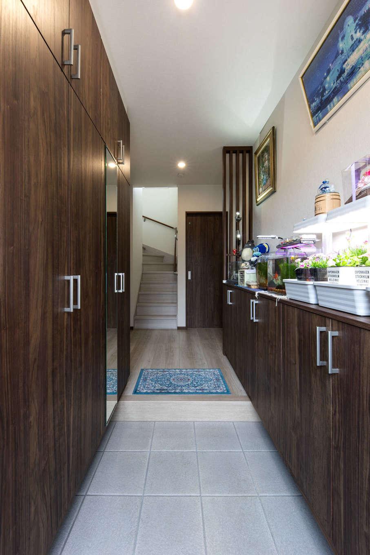 建築システム(狭小住宅専門店)【収納力、二世帯住宅、ガレージ】二世帯共用の玄関。天井まで届く大容量のシューズクロークで、家族の靴をすっきりと収納する。片方は、水槽を置けるよう下段のみにして、ちょっとした趣味のコーナーに