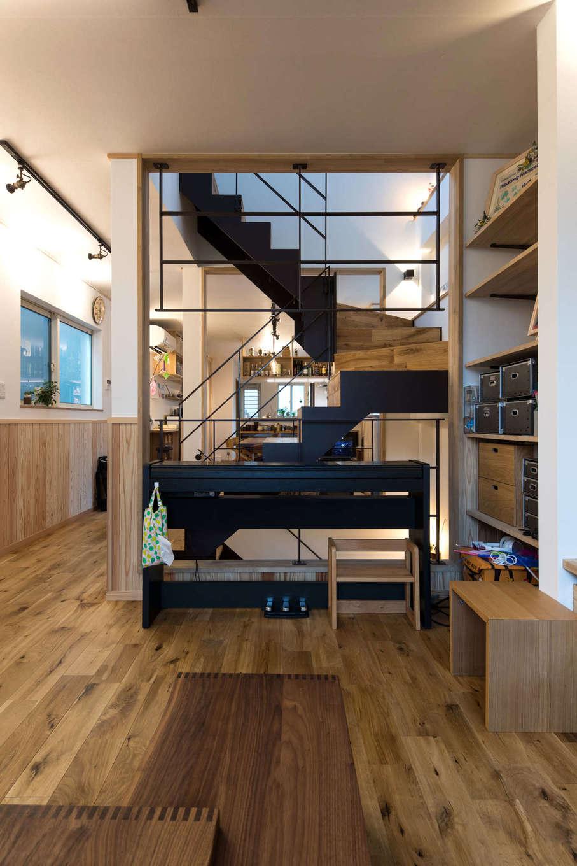 建築システム(狭小住宅専門店)【収納力、狭小住宅、鉄骨鉄筋コンクリート構造】空間を緩やかに仕切るのは鉄骨階段。手前はリビング、階段の奥にダイニングとキッチンが広がる。床には自然の風合いを活かした無塗装のナラ無垢材を。天井は土佐和紙を張った
