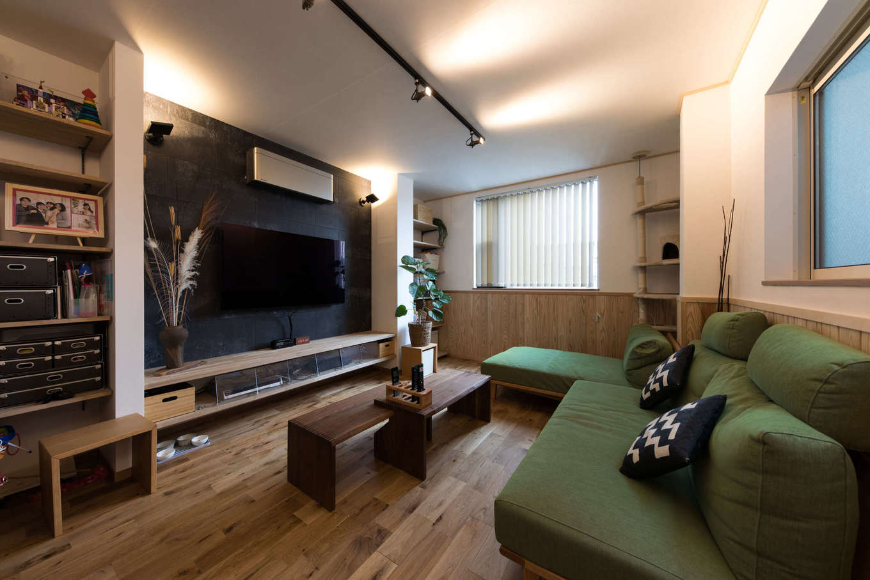 建築システム(狭小住宅専門店)【収納力、狭小住宅、鉄骨鉄筋コンクリート構造】リビングはシックなインテリアに。テレビボードも床材と同じナラ材で造作、壁をアイアンブラックにしたことでテレビが悪目立ちしない、くつろぎにふさわしい空間に仕上がっている。明かりはすべて間接照明に