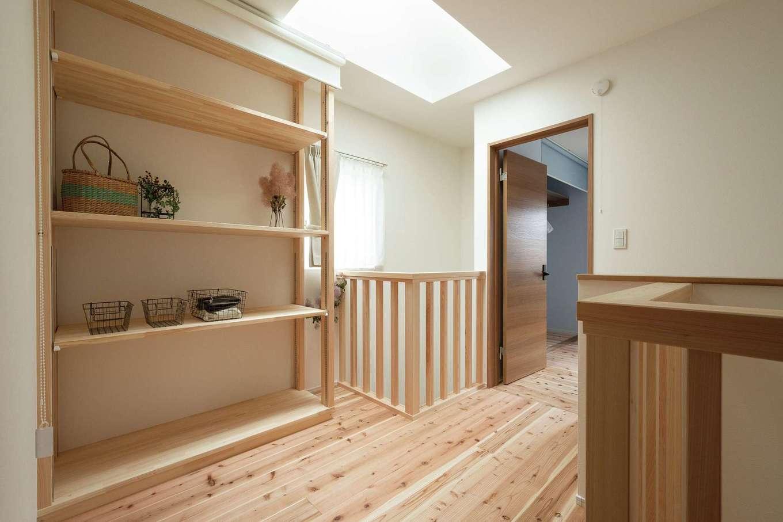 片川工務店【自然素材、狭小住宅、間取り】2階のトップライトから差し込む光は、吹き抜けを通して階下の玄関ホールに届く。必要に応じてロールスクリーンで目隠しする収納棚は造作で仕上げた