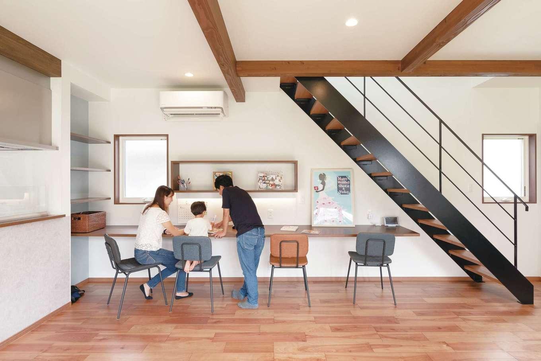 ホームプラザ大東【デザイン住宅、子育て、収納力】「子どもが大きくなっても自然に顔を合わせるようにしたい」というご主人の希望で階段はリビングインスタイルに。宿題だけでなく、パソコンや仕事にも使えるよう、カウンターは長めにしてもらった。教科書などを置ける棚の下の壁は、マグネットがつくようになっている