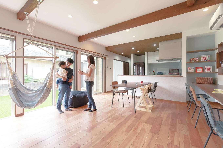ホームプラザ大東【デザイン住宅、子育て、収納力】大きく開かれた窓から光と開放感が運ばれ、実際の広さ以上の大らかさで満たされるLDK。梁やカウンターには濃いブラウンを選び、落ち着きを添えた。床は掃除のしやすいタイプを選択。建具も溝や段差のない吊り戸が使われている。展示場を巡っている際に気に入ったハンモックを採用