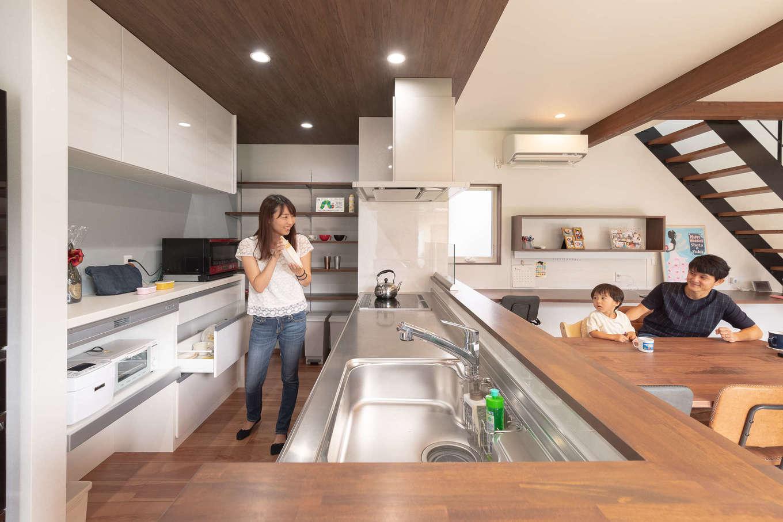 ホームプラザ大東【デザイン住宅、子育て、収納力】天井の高さと色を変え、穏やかに役割が分割されたキッチン。玄関の出入りから階段の上り下り、庭で遊ぶ姿や和室でのお昼寝の様子まで、家事をしながら確認することができる。奥の造作棚は高さ可変で、下部にゴミ箱を置くことも想定されている