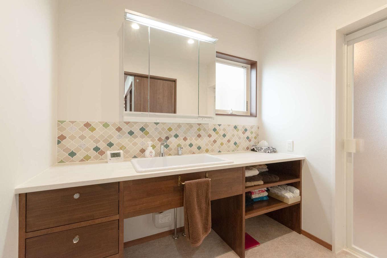 ホームプラザ大東【デザイン住宅、子育て、収納力】タイルでかわいさを添えた造作洗面台は、朝の準備で渋滞しないよう幅が広く取られた。流しも医療用の大きなサイズのものが選ばれている。左手には室内物干しとアイロン掛け用のカウンターが備えられた家事室。浴室から外の物干し場までが一直線で結ばれ、洗濯の効率を高めている