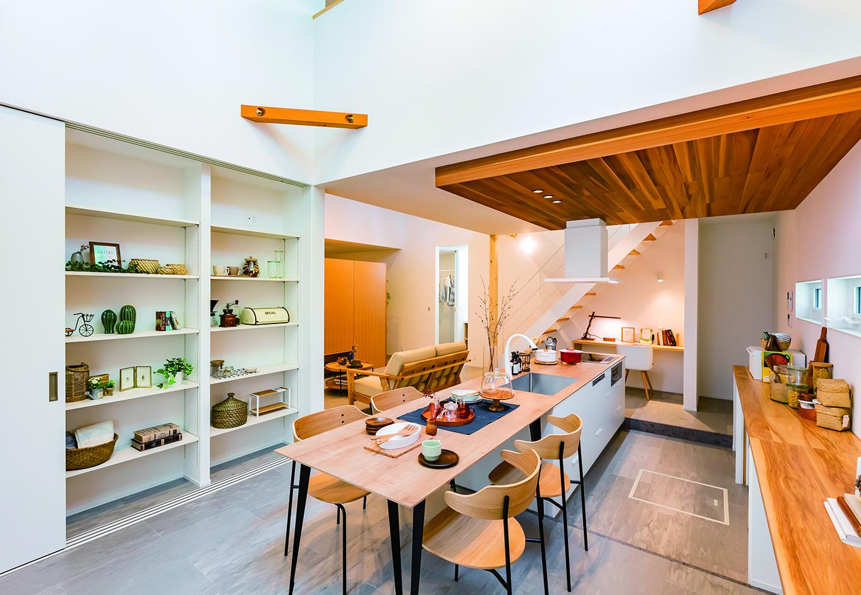 ARRCH アーチ【浜松市中区富塚町2961-11・モデルハウス】フロアを一段下げてキッチンとダイニングテーブルを一体型にし、すっきりとしたデザインに。カウンターがフラットなのでキッチンの使い勝手も向上するダイニングキッチンの背面には大きな扉の収納庫を配置。生活感を隠して常に空間を美しくキープできる