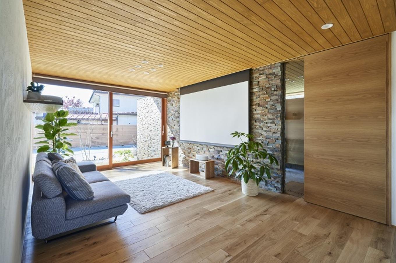 KESHIKI YAMANASHI【デザイン住宅、夫婦で暮らす、平屋】外壁から続く印象的な石張りの壁のあるリビング。大きな木製窓いっぱいに庭の木々が映え、四季の移ろいを感じられる