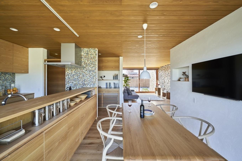 KESHIKI YAMANASHI【デザイン住宅、夫婦で暮らす、平屋】キッチンカウンターの手前にも収納スペースを設け、すっきりとしたキッチンダイニングに。キッチンに立ちながらテレビも大画面見られるから、台所仕事が多い奥様には嬉しいポイント