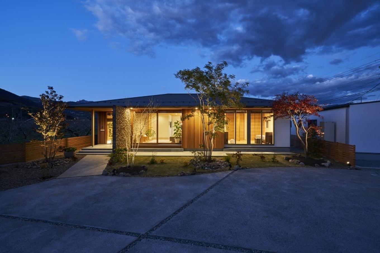 KESHIKI YAMANASHI【デザイン住宅、夫婦で暮らす、平屋】夜には雰囲気が一転。ライトアップされた庭の木々と、建物の重厚感がワンランク上の住まいを演出