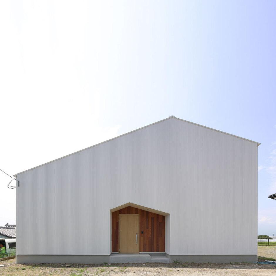 Um House(マル祐戸田建築)【SIMPLE NOTE(シンプルノート)】屋根のラインと同じ形に玄関の壁を切り取り、シンプルな中にも個性を強調した外観デザイン。玄関ポーチは板張りにして変化を付けている