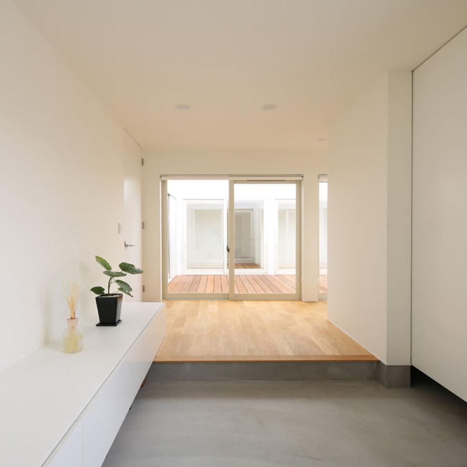 Um House(マル祐戸田建築)【SIMPLE NOTE(シンプルノート)】コンクリートの土間と白い内装、無垢の床で構成された玄関。室内の随所に適量の収納が設けることで、常に整然とした空間をキープできる