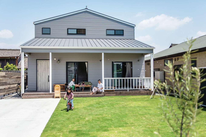 CLASSICA HOME/クラシカホーム【デザイン住宅、子育て、自然素材】夫婦の夢を叶えたアメリカンサーファーズハウス。休日はカヴァードポーチでおうちごはんを楽しむ。広い芝生の庭でBBQや子どもプールもやりたい放題! グレーの屋根と外壁はメンテナンス負担の少ないガルバリウム鋼板を採用