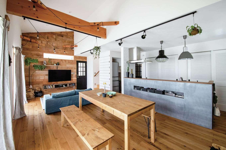 CLASSICA HOME/クラシカホーム【デザイン住宅、子育て、自然素材】海が見えるリゾート地のカフェをイメージしたLDK。床は無垢オーク材、天井と壁は漆喰。テレビの背面に古材を貼ってヴィンテージ感を出した。モルタル調のキッチンにインダストリアルなペンダントライトが似合う