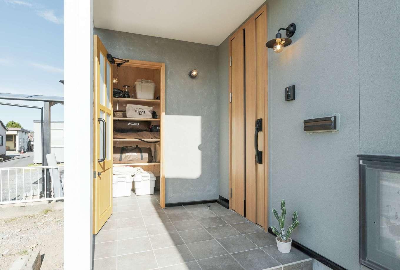 ホームプラザ大東 建物の西側に新たに設けられた子世帯の玄関。周囲は塗り壁とし、住まい手のセンスを伝えるナチュラル感ある仕上がりに。アウトドアグッズ用の収納庫部分は増築。上部は物干しスペースで、玄関の出入りも雨に濡れずに済む
