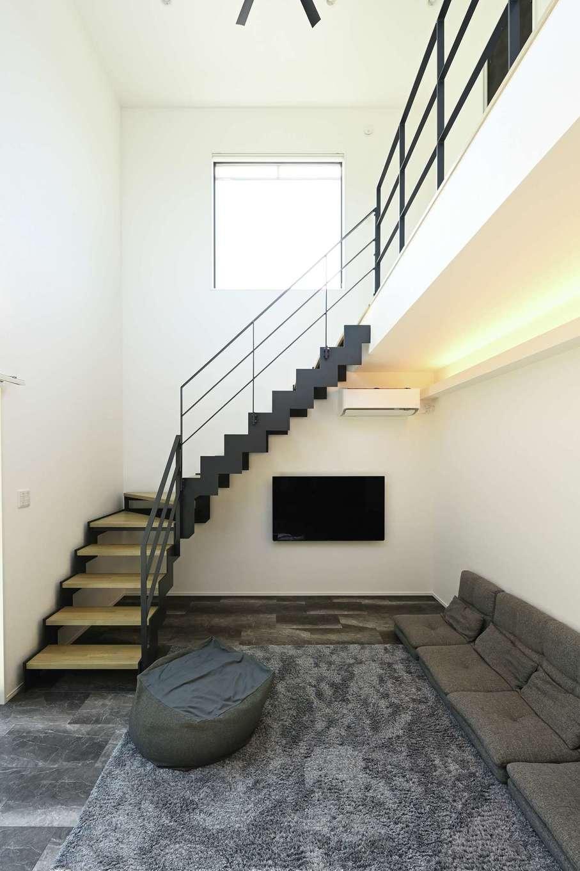 内田建設【デザイン住宅、間取り、スキップフロア】アイアン階段が印象的なリビングダイニング。高さ5.5mの吹き抜けと、窓から注ぐ光が開放感を演出する。断熱などの基本性能が高く、エアコンの効きがいいのも魅力だ