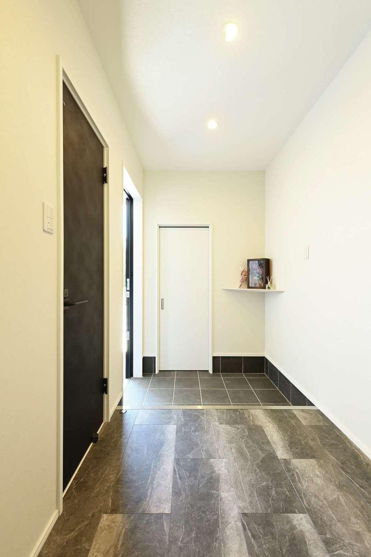 内田建設【デザイン住宅、間取り、スキップフロア】モノトーンでコーディネートした玄関。白い扉を開けると大容量のシューズクロークへ。黒い扉の先は寝室になっている
