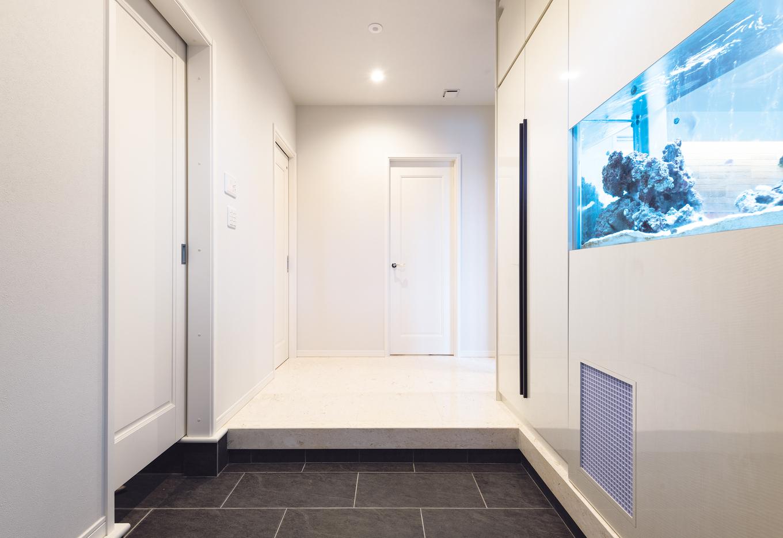 ウィザースホーム【1000万円台、デザイン住宅、子育て】熱帯魚が出迎える玄関ホールは、家族を癒し、来客にサプライズを演出。内装は白で統一し、アクアリウムのクリアなブルーを引き立てている