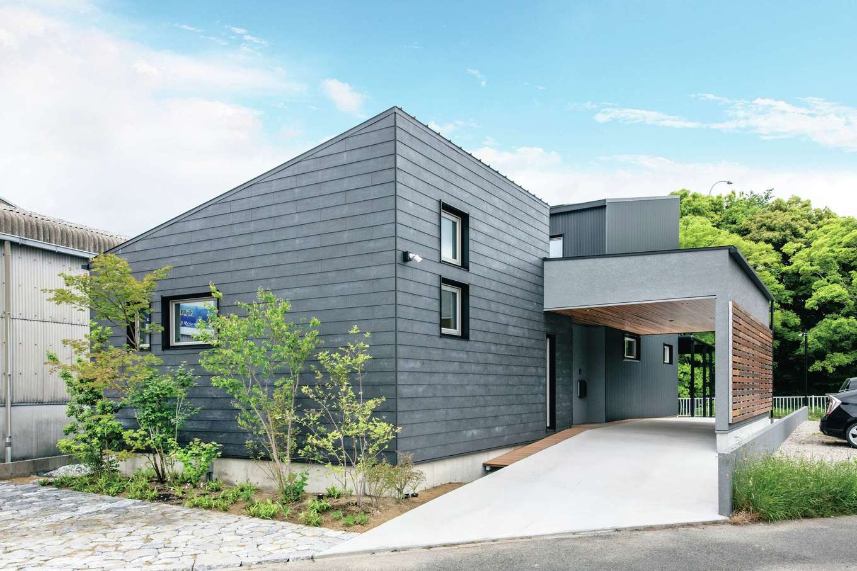 ainoa.life くらはし建築【デザイン住宅、間取り、インテリア】屋根付きのエントランスがある角張ったフォルムがクールな外観。濃いグレーのガルバリウム鋼板で外壁を統一し、ガレージの天井を板張りにしてアクセントをつけた