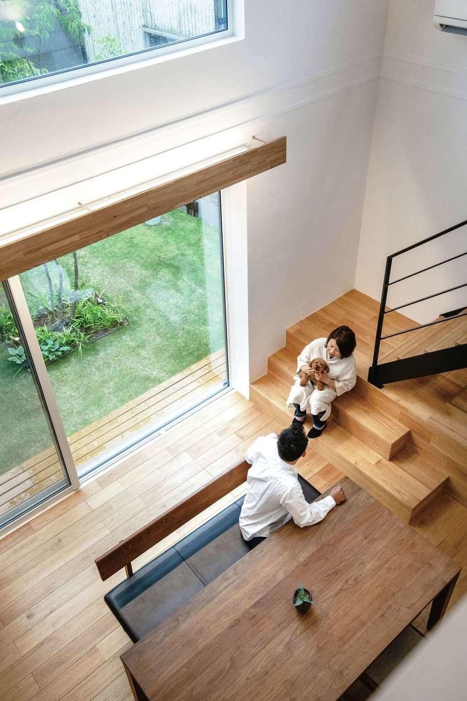 ainoa.life くらはし建築【デザイン住宅、間取り、インテリア】吹き抜けのダイニングで中庭を眺めながら、愛犬と一緒にひと休み。クルミの無垢の床の感触が心地よい。オリジナルの換気システムによって家の中の空気をクリーンに保ち、愛犬のニオイも気にならない