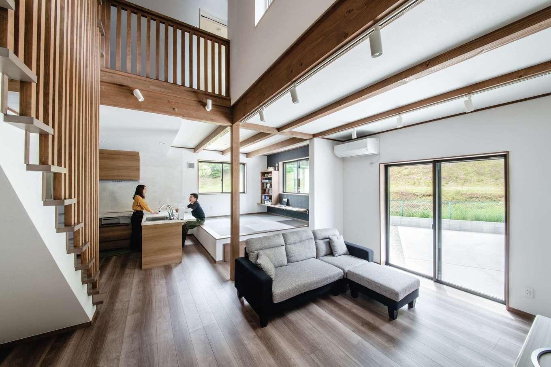 山脇木材【趣味、間取り、ガレージ】吹き抜けのあるLDK。リビング階段の手すりや化粧梁を無垢材で統一し、ダイナミックで上質感あふれる空間が実現。L型のオープンキッチンはテーブルを兼ね、対面の小上がりに座って食事できる