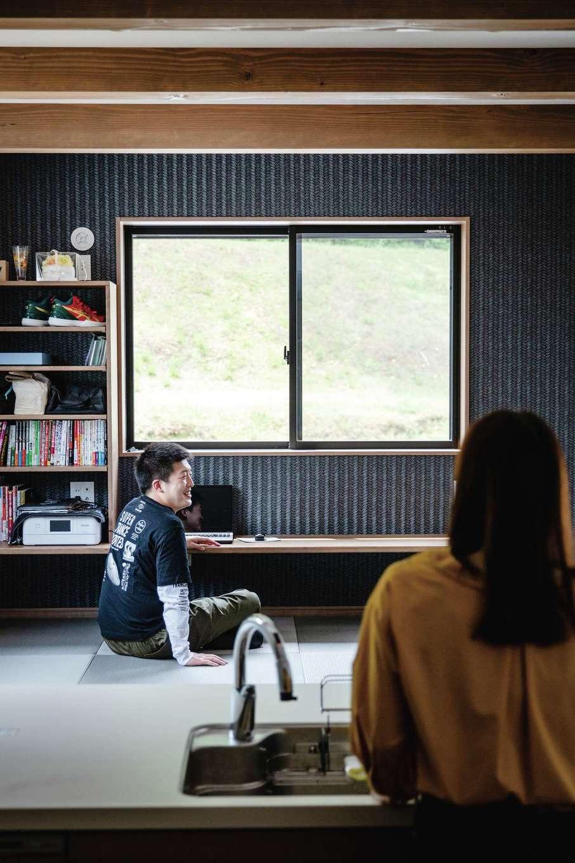 山脇木材【趣味、間取り、ガレージ】キッチンの間の前に小上がりがあり、調理や片付けをしながら夫婦で会話を楽しむことも。ご主人は小上がりでゴロゴロするのがお気に入り。カウンターの書棚にはバスケットボール関係の本がずらり