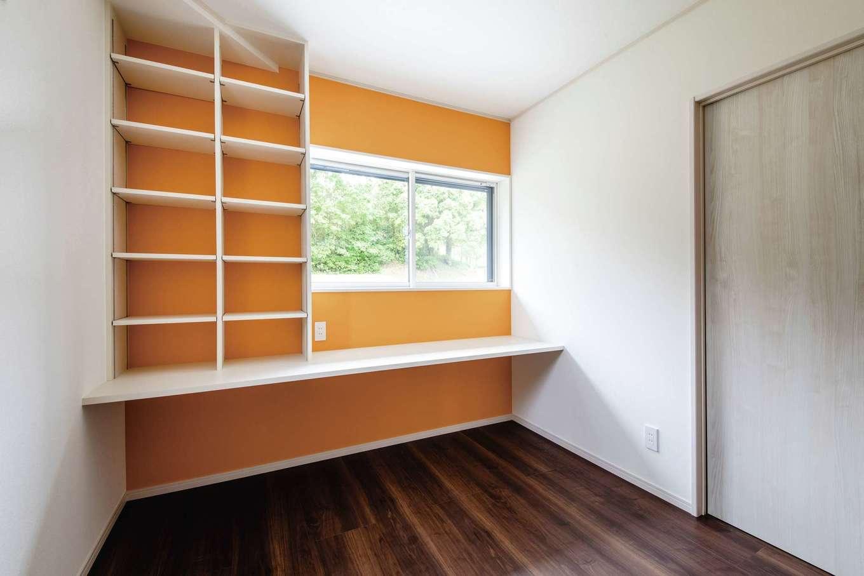 山脇木材【趣味、間取り、ガレージ】将来の子ども部屋のクロスには、バスケチームのイメージカラーを採用。オレンジ色が室内をいっそう明るい雰囲気にしている。学習机代わりのカウンターと、書棚もたっぷり設けてある。窓から見える景色も緑が美しい