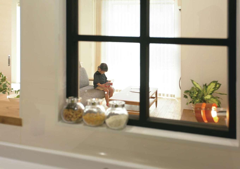 キッチンのIHコンロの前には四角い小窓をオーダー。油ハネを防止しながら、リビングにいる子どもの様子がわかる優れもの