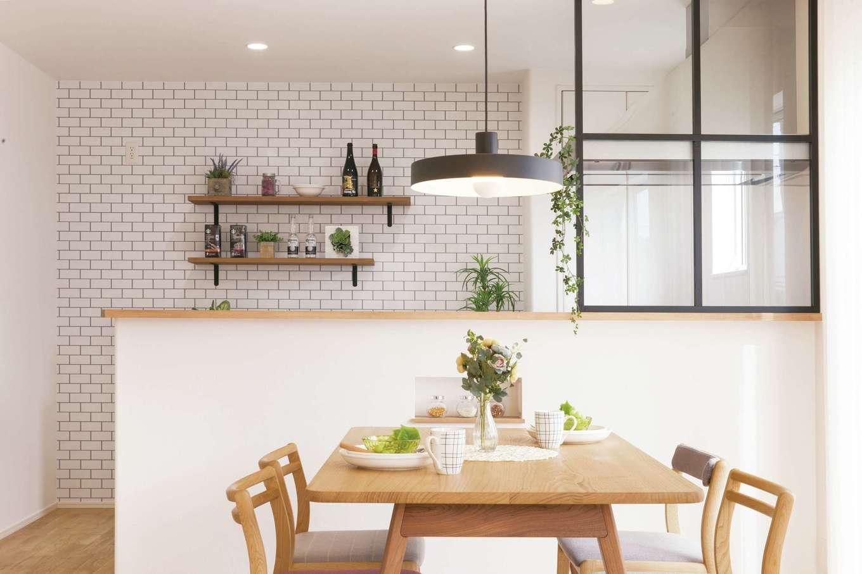 無垢の木と白い壁にアクセントを加えるのが、ブラックのアイアン。キッチンの造作窓や、夫妻が選び抜いた「flame」の照明が似合う