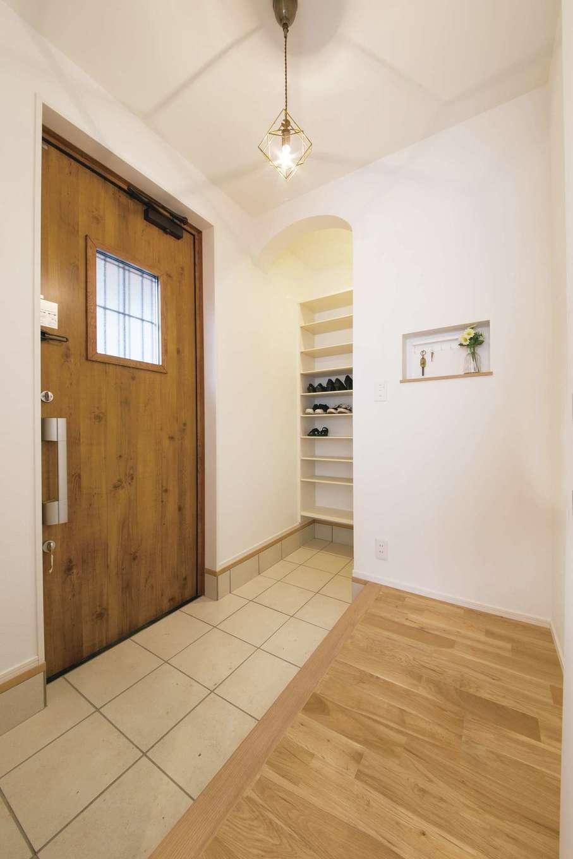 木調ドアが似合う玄関ホール。シューズクロークへの入り口もR型のデザインを採用した