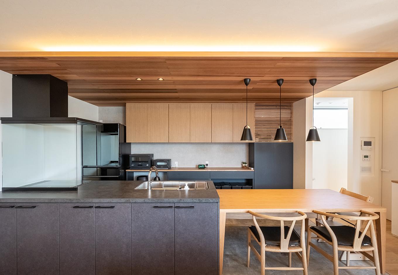 金子工務店/めぐみ不動産(アイフルホーム 沼津店)【デザイン住宅、子育て、建築家】木の温もりとアイアンブラックのマテリアル感で、大人の空間に仕上げたダイニングキッチン。キッチンに横付けのダイニングテーブルは、子どものスタディスペースなどマルチに活躍する