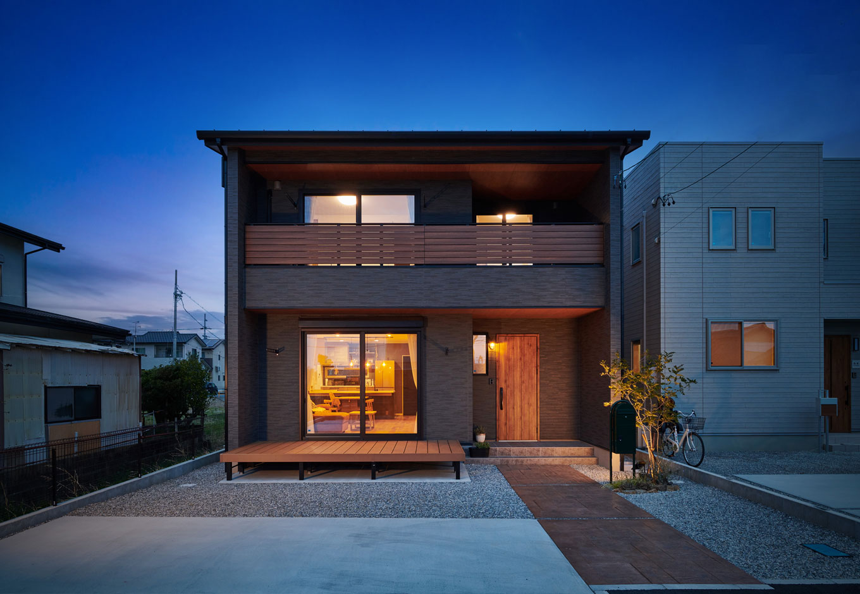 子育て安心住宅【1000万円台、デザイン住宅、子育て】太陽光発電パネルを載せやすい屋根形状にも配慮し、同社が提案したモダンな外観。「木を見せたい」という要望に合わせて軒天には木を貼ったり、玄関ドアとインナーバルコニー前の格子も木目がアクセントになるものを選ぶなど、ディテールにもセンスが光る