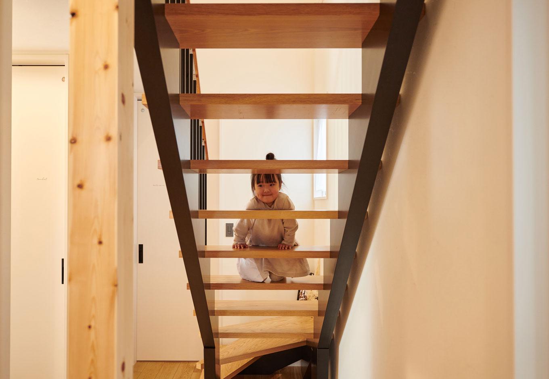子育て安心住宅【1000万円台、デザイン住宅、子育て】木×アイアンの階段がインテリアのように映える玄関ホール。階段は蹴込み板のないスケルトン設計で視線が奥まで抜ける分、空間がより広く感じられる。柱を3本連続して並べてアクセントにすることで、空間をよりナチュラルに演出している