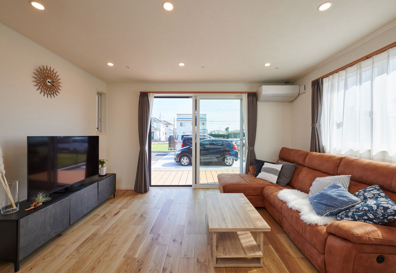 子育て安心住宅【1000万円台、デザイン住宅、子育て】「陽光がたっぷり入る家に」というTさんのイメージがカタチになった、2面採光の明るいリビング。掃き出し窓の先には室内の床面と高さを合わせたデッキ空間が広がり、リビングの一部のように使える。部屋干しができるよう、窓際に室内天井物干しを取り付けてあるのもポイント